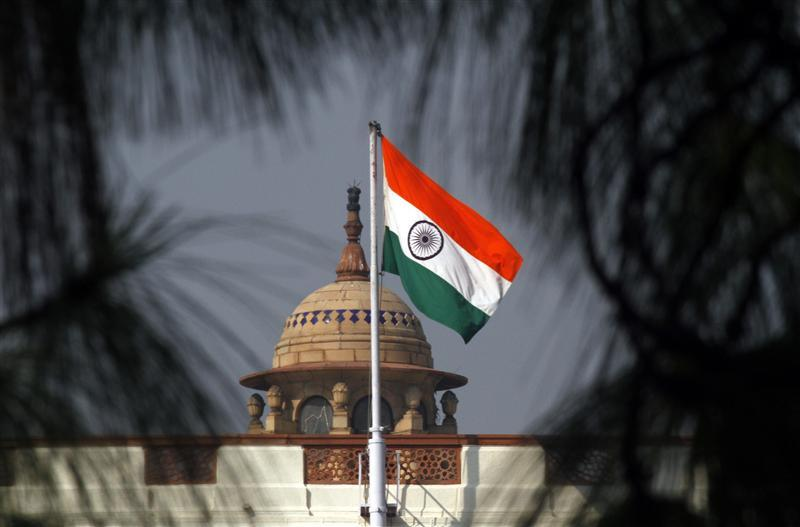 An Indian national flag flutters on top of the Indian parliament building in New Delhi December 1, 2010. The Indian parliament on Wednesday approved a $9.8-billion additional spending bill to cover various payments including outstanding government debt, food and fertiliser subsidies, and government pensions. The bill was passed by a voice vote in parliament, a type of vote allowing the government to bypass a three-week deadlock between the ruling Congress party-led coalition and opposition parties caused by rows over a series of corruption scandals. REUTERS/B Mathur (INDIA - Tags: POLITICS BUSINESS)