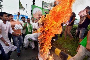 Patna: RJD activists burning an effigy of Bihar Chief Minister Nitish Kumar during a protest against Bhagalpur Srijan scam in Patna on Friday. PTI Photo(PTI8_18_2017_000090A)