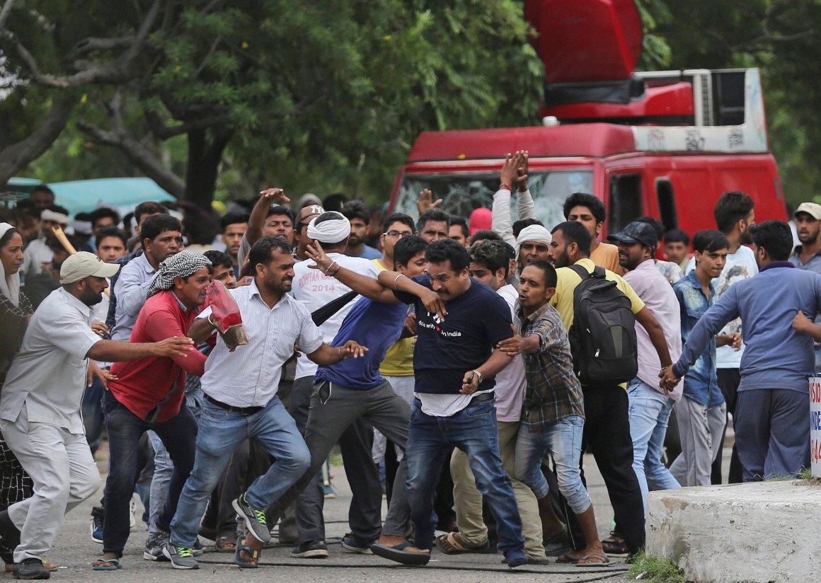 Panchkula: Supporters of the Dera Sacha Sauda sect attack a member of the media, foreground wearing a blue dark t-shirt, in Panchkula on Friday. PTI Photo(PTI8_25_2017_000148B)
