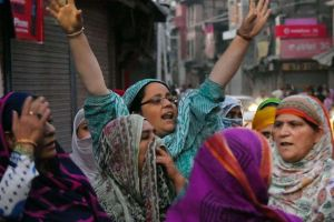 Women shout slogans and block a road during a protest against braid choping incidents in Srinagar valley. PTI