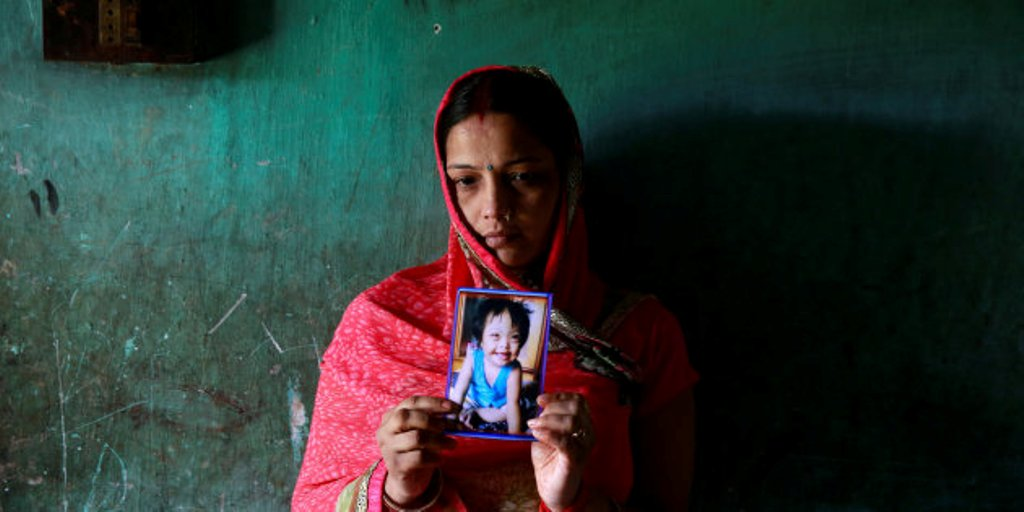 Rinki Singh, 31, holds a photo of her daughter Aarushi, 6, who died in the intensive care unit (ICU) of the Baba Raghav Das hospital in the Gorakhpur district, India August 14, 2017. REUTERS/Cathal McNaughton