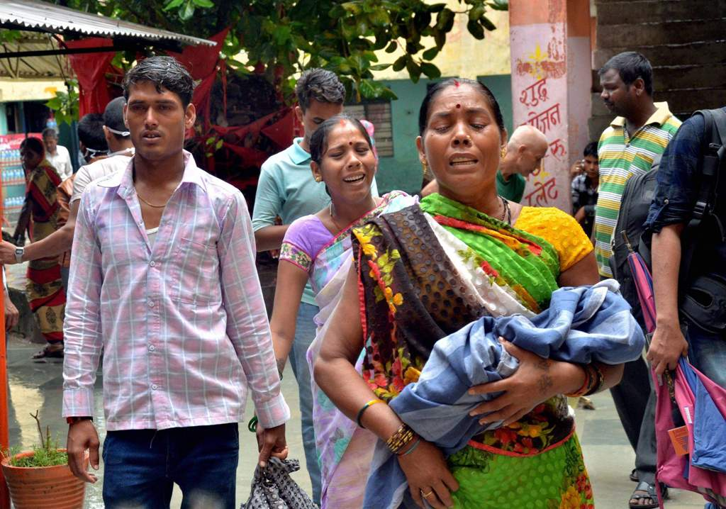 Relatives carry a child at the Baba Raghav Das Medical College Hospital where over 60 children have died over the past one week in Gorakhpur district in August. PTI