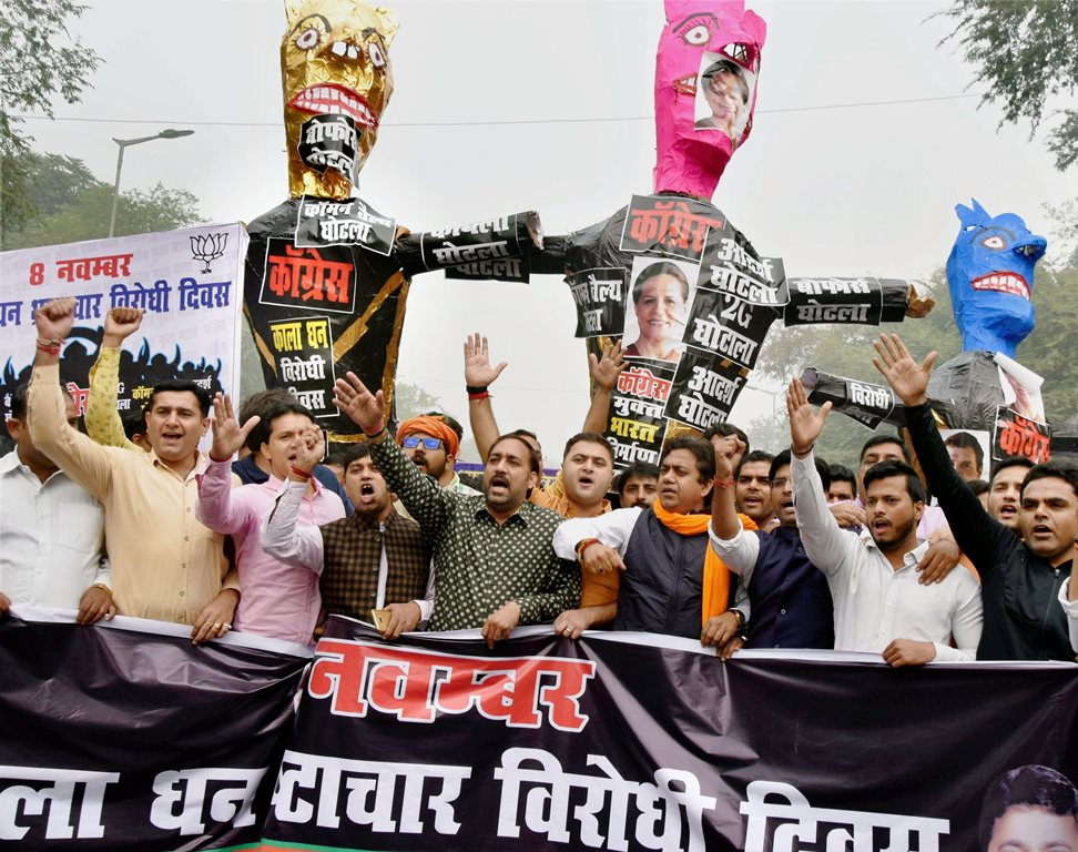 New Delhi: Bharatiya Janata Yuva Morcha members carry effigies representing Congress party during their Anti-Black Money Day rally on the anniversary of demonetisation announcement, in New Delhi on Wednesday. PTI Photo (PTI11 8 2017 000103A)