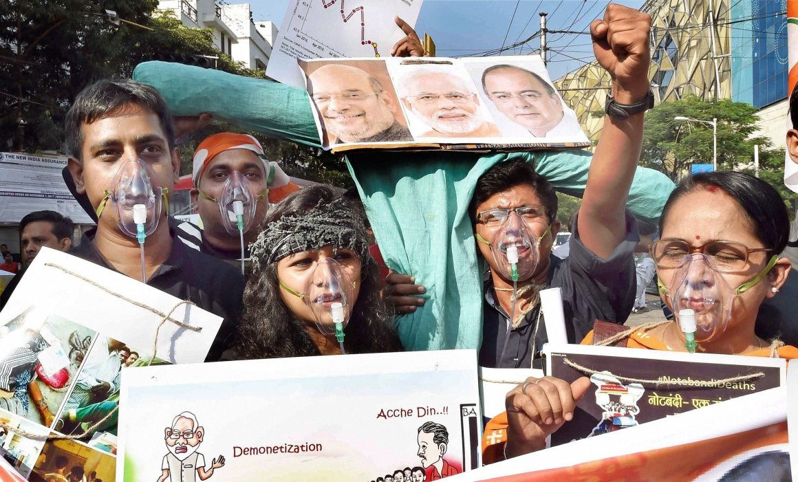 Kolkata: Congress activists wear oxygen masks during a protest rally on the 1st anniversary of demonetisation move, in Kolkata on Wednesday. PTI Photo by Ashok Bhaumik (PTI11_8_2017_000201B)