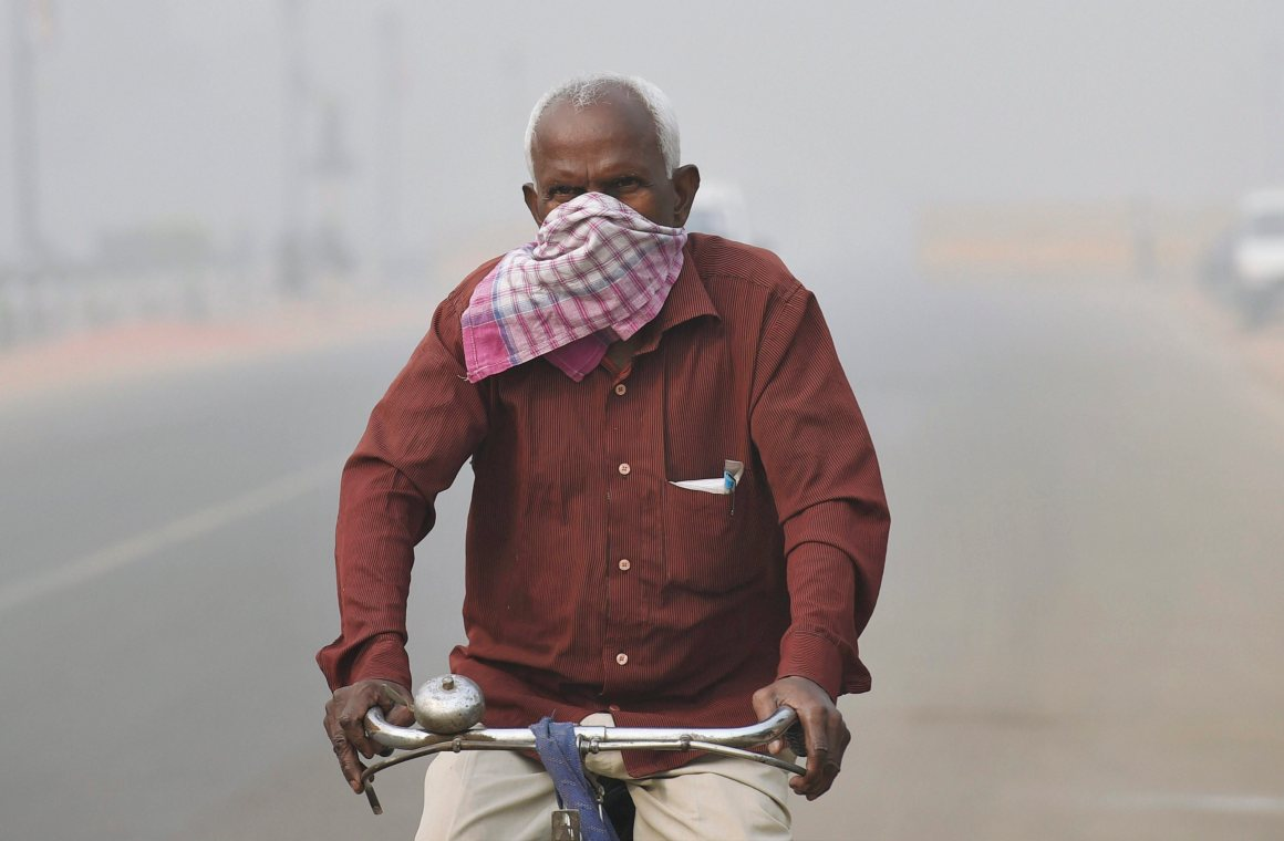 New Delhi: A man covers his nose with a handkerchief to protect himself from heavy smog and air pollution while cycling on the road near India Gate, in New Delhi on Friday. PTI Photo by Kamal Singh(PTI11_10_2017_000030B)