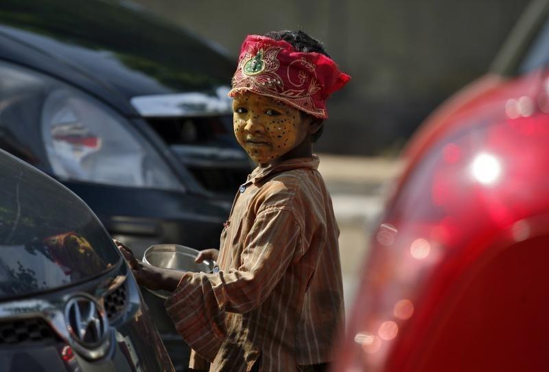 Suman, a nine-year-old nomad girl from Rajasthan, with her face painted in colours to attract commuters, looks at the camera as she begs for alms at a traffic junction in Noida on the outskirts of New Delhi October 13, 2011. REUTERS/Parivartan Sharma/File Photo