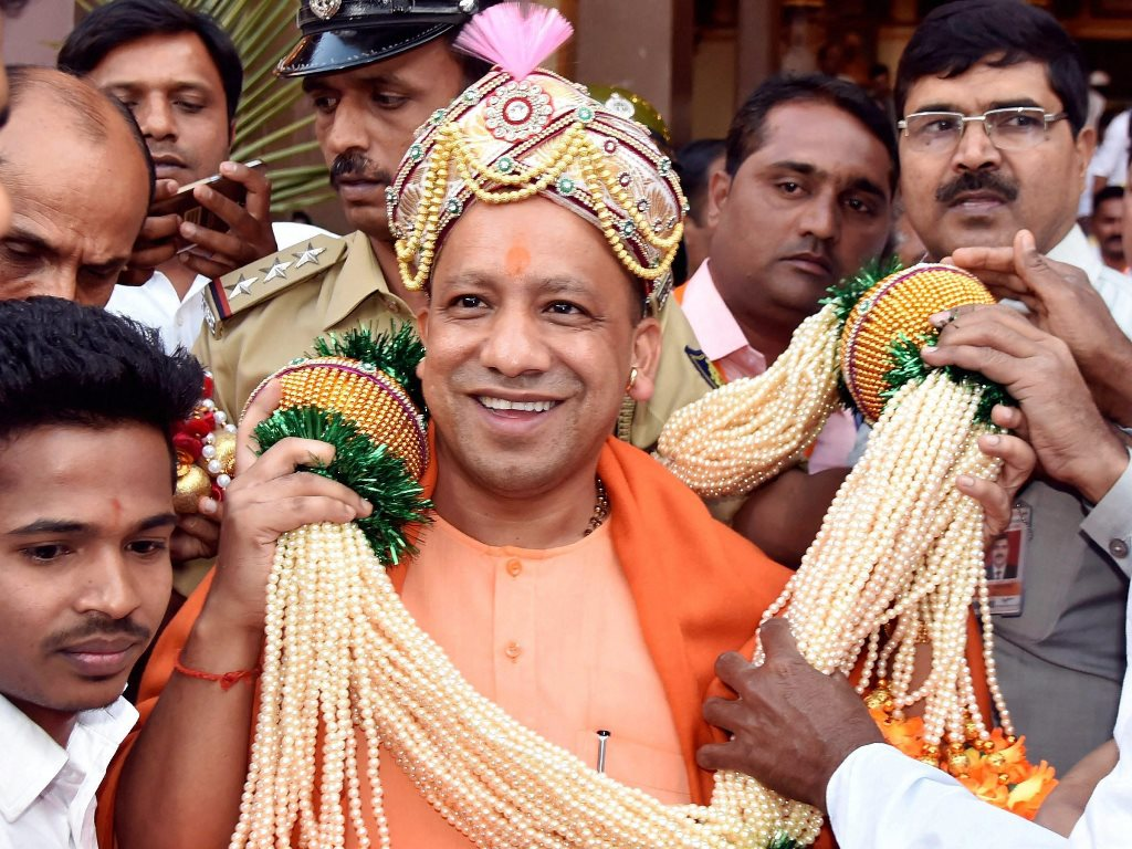 Hubbali: Uttar Pradesh Chief Minister Yogi Adityanath being garlanded at a public meeting during the Karnataka BJP chief BS Yeddyurappa's Parivartan Yatra in Hubbali on Thursday. PTI Photo (PTI12_21_2017_000206B)
