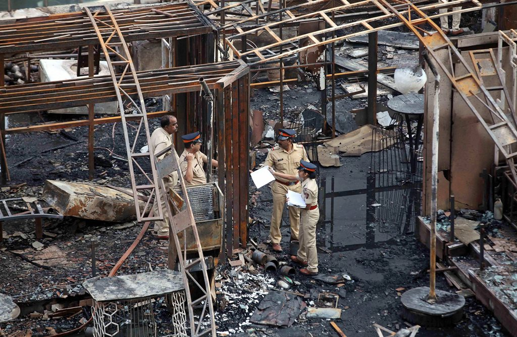 Mumbai: A team of police inspect the debris after a fire broke out in Mumbai on Friday. At least 14 people were killed and as many injured after a major fire in Kamala Mills Compound in Lower Parel. PTI Photo (PTI12_29_2017_000032B)