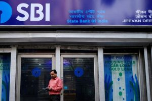 A man checks his mobile phones in front of State Bank of India (SBI) branch in Kolkata, February 9, 2018. REUTERS/Rupak De Chowdhuri