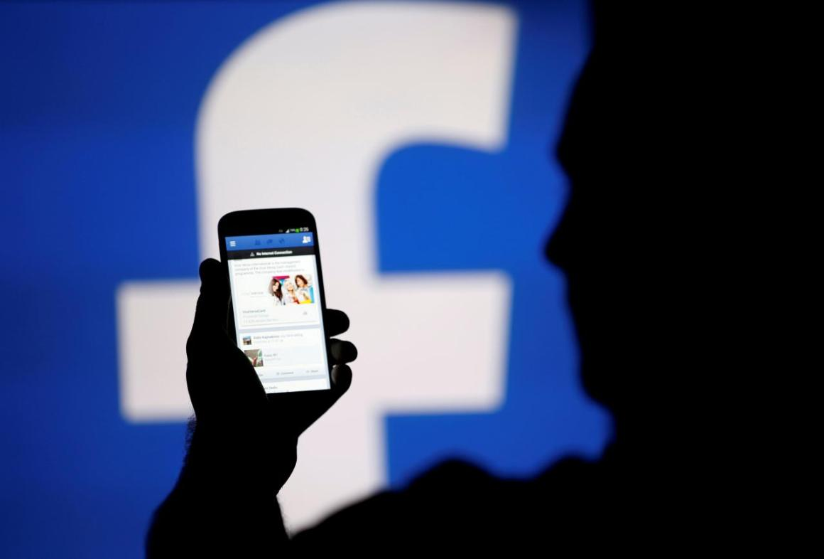 FILE PHOTO: A man is silhouetted against a video screen with an Facebook logo as he poses with an Samsung S4 smartphone in this photo illustration August 14, 2013. REUTERS/Dado Ruvic/File Photo