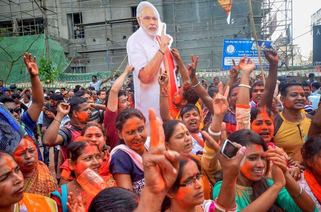 Agartala: BJP supporters hold up a placard of Prime Minister Narendra Modi after party's victory in Tripura Assembly elections results in Agartala on Saturday. BJP's win marks an end to 25 years of CPI-M government rule in the state. PTI Photo. PTI Photo (PTI3_3_2018_000097B)
