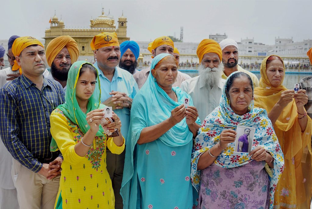 **FILE PHOTO** Amritsar: In this file photo dated 19 June, 2014, family members show photographs of the Indians who are believed to be trapped in Mosul, Iraq at Golden Temple in Amritsar. External Affairs Minister Sushma Swaraj in a statement made at Rajya Sabha today, stated that the 39 bodies exhumed from a mount in Badoosh in Iraq have been identified as those of abducted Indians and will be brought back to India on a special plane. PTI Photo (PTI3_20_2018_000074B)