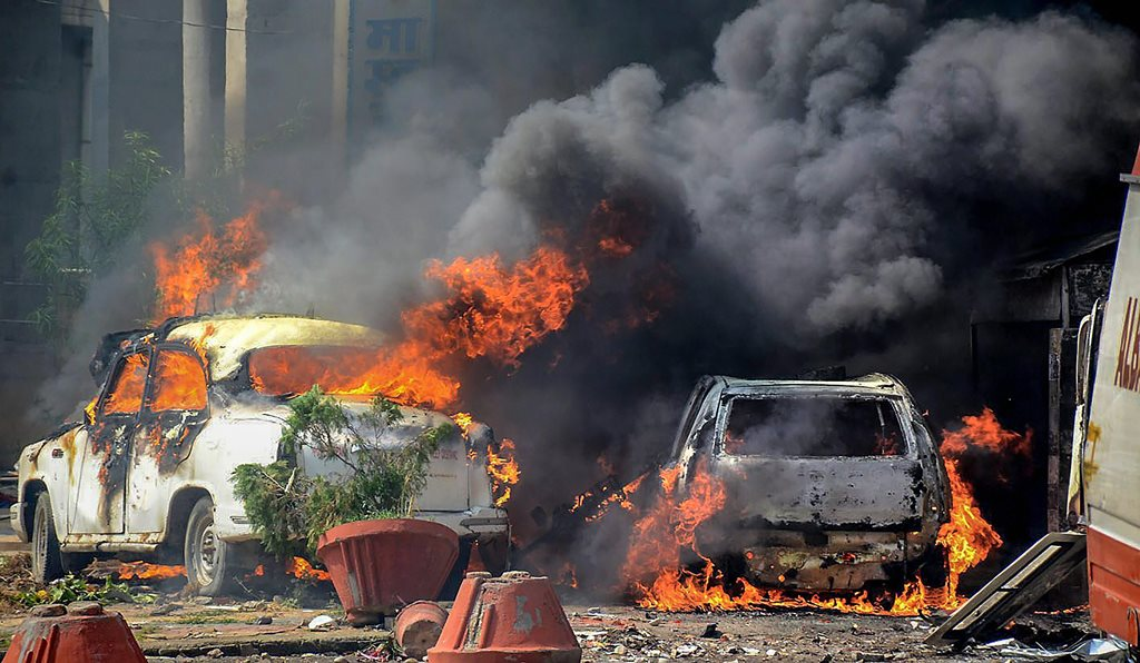 Muzzaffarnagar: Smoke billows out of burning cars during 'Bharat Bandh' against the alleged 'dilution' of Scheduled Castes/Scheduled Tribes act, in Muzzaffarnagar on Monday. PTI Photo (PTI4_2_2018_000236B)