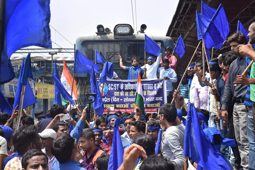 Patna: Bhim Army Sena members stop a train during 'Bharat Bandh' call given by Dalit organisations against the alleged 'dilution' of the Scheduled Castes and Scheduled Tribes act, in Patna on Monday. PTI Photo(PTI4_2_2018_000043B)