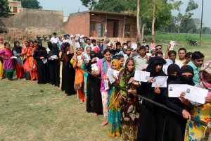 Bijnor: Burqa-clad women, along with other voters, show their voter identity cards as they wait to cast thier votes for Noorpur Assembly bypolls, in Bijnor, on Monday, May28, 2018. (PTI Photo) (PTI5_28_2018_000075B)
