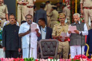 RPT with add info::: Bengaluru: Karnataka Governor Vajubhai Vala administers the oath to JD(S) leader H D Kumaraswamy as Karnataka Chief Minister during the swearing-in ceremony of JD(S)-Congress coalition government, in Bengaluru, on Wednesday. (PTI Photo/Shailendra Bhojak) (PTI5_23_2018_000130B)