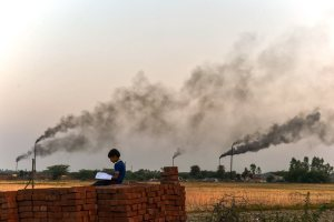Kanpur: A child reads from a book, as thick black smoke rises in the sky from the glue factories at Dakari village of Unnao district near Kanpur on Friday. The World Health Organisation global air pollution database has revealed that India has 14 of the 20 most polluted cities in the world in terms of Particulate Matter (PM) 2.5 concentration, with Kanpur topping the charts. It said that nine out of 10 people in the world breathe air containing high levels of pollutants. PTI Photo by Arun Sharma(PTI5_6_2018_000146B)