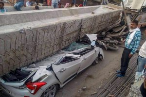 Varanasi: People gather near cars crushed after a portion of an under-construction flyover collapsed, leaving at least 12 feared dead, in Varanasi on Tuesday. (PTI Photo)(PTI5_15_2018_000159B)