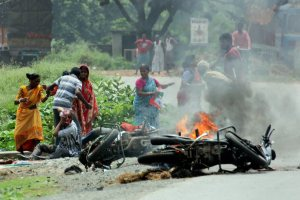 Nadia: People injured in poll violence sit by the side of a road as a vehicle is set on fire by locals during Panchayat polls, in Nadia district of West Bengal on Monday. (PTI Photo) (PTI5_14_2018_000125B)