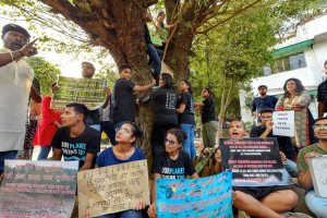 New Delhi: Activists from various environmental organisations display placards and hold a tree during a protest against cutting of trees in Nauroji Nagar area, in New Delhi on Sunday evening, June 24, 2018. (PTI Photo/Kamal Kishore) (PTI6_24_2018_000133B)