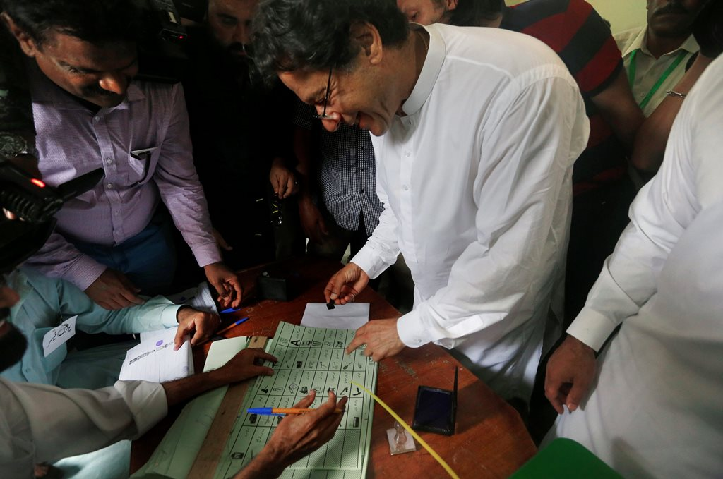 Islamabad: Pakistani politician Imran Khan, center, chief of Pakistan Tehreek-e-Insaf party, casts his vote at a polling station for the parliamentary elections in Islamabad, Pakistan, Wednesday, July 25, 2018. After an acrimonious campaign, polls opened in Pakistan on Wednesday to elect the country's third straight civilian government, a first for this majority Muslim nation that has been directly or indirectly ruled by its military for most of its 71-year history.AP/PTI(AP7_25_2018_000058B)