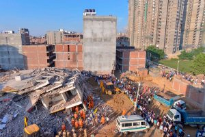 Greater Noida: Rescue workers carry the body of a victim at the site of a collapsed building at Shahberi village, in Greater Noida West on Wednesday, July 18, 2018. A six-storey under-construction building collapsed in Greater Noida, killing at least two persons and trapping several others under the debris. (PTI Photo)  (Story no DES49)(PTI7_18_2018_000012B)
