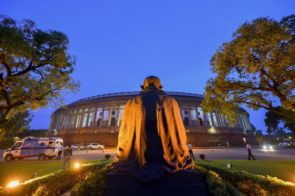 New Delhi: The statue of Mahatma Gandhi in the backdrop of the Parliament House during the Monsoon Session, in New Delhi on Friday, July 20, 2018. (PTI Photo/Kamal Kishore) (PTI7_20_2018_000250B)