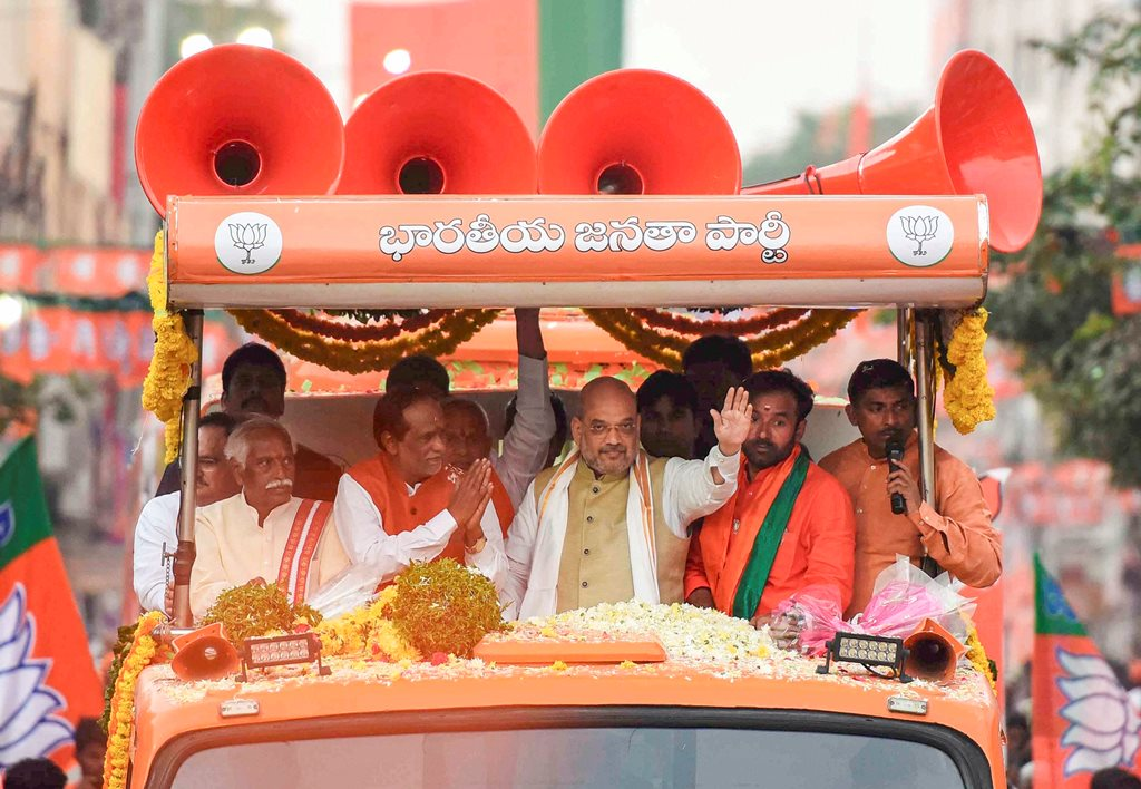 Musheerabad: BJP President Amit Shah waves at the crowd during a road show during an election campaign in favor of party leaders Dr K Laxman and Bandaru Dattatreya, in Musheerabad, Wednesday, Nov. 28, 2018. (PTI Photo) (PTI11_28_2018_000203B)