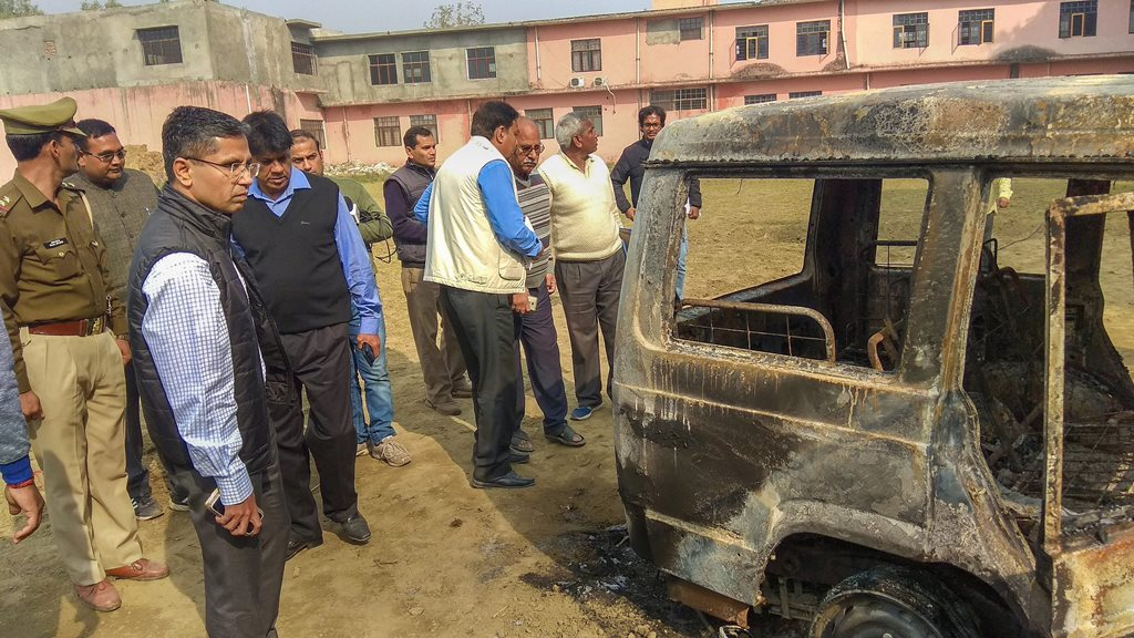 Bulandshahr: Policemen inspect vehicles set on fire by a mob yesterday during a protest over the alleged illegal slaughter of cattle, in Bulandshahr, Tuesday, Dec. 04, 2018. Four persons were arrested today after police lodged an FIR against over two dozen people for rioting and murder in connection with the violence, according to officials. (PTI Photo) (PTI12_4_2018_000040B)