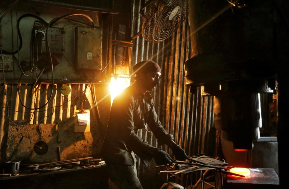 A worker operates a hydraulic press machine at a workshop manufacturing flanges for automobiles in Mumbai, India, May 29, 2017. REUTERS/Shailesh Andrade/File Photo