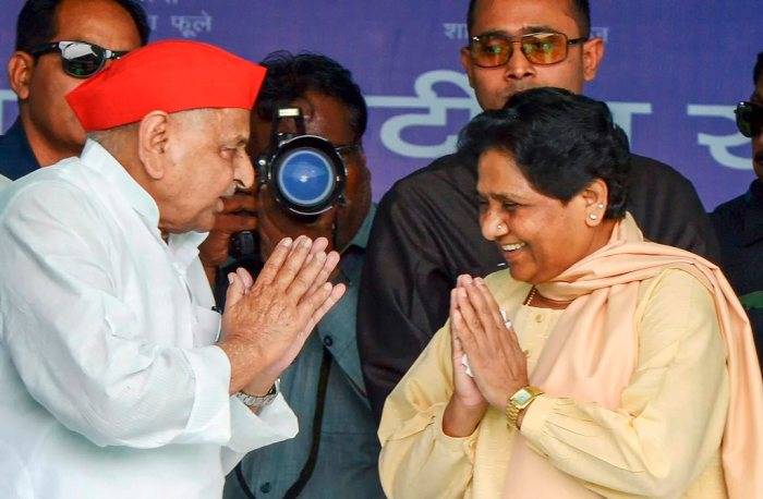 Mainpuri: Samajwadi Party patron Mulayam Singh Yadav exchanges greetings with Bahujan Samaj Party supremo Mayawati as SP President Akhilesh Yadav looks on during their joint election campaign rally in Mainpuri, Friday, April 19, 2019. Mulayam Singh Yadav and Mayawati have been bitter rivals since 1995 when SP cadres allegedly attacked the state guest house where the BSP chief had been camping with her supporters. (PTI Photo) (PTI4_19_2019_000086B)