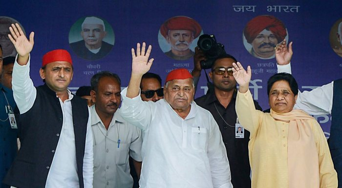 Mainpuri: Samajwadi Party patron Mulayam Singh Yadav exchanges greetings with Bahujan Samaj Party supremo Mayawati as SP President Akhilesh Yadav looks on during their joint election campaign rally in Mainpuri, Friday, April 19, 2019. Mulayam Singh Yadav and Mayawati have been bitter rivals since 1995 when SP cadres allegedly attacked the state guest house where the BSP chief had been camping with her supporters. (PTI Photo) (PTI4_19_2019_000089B)