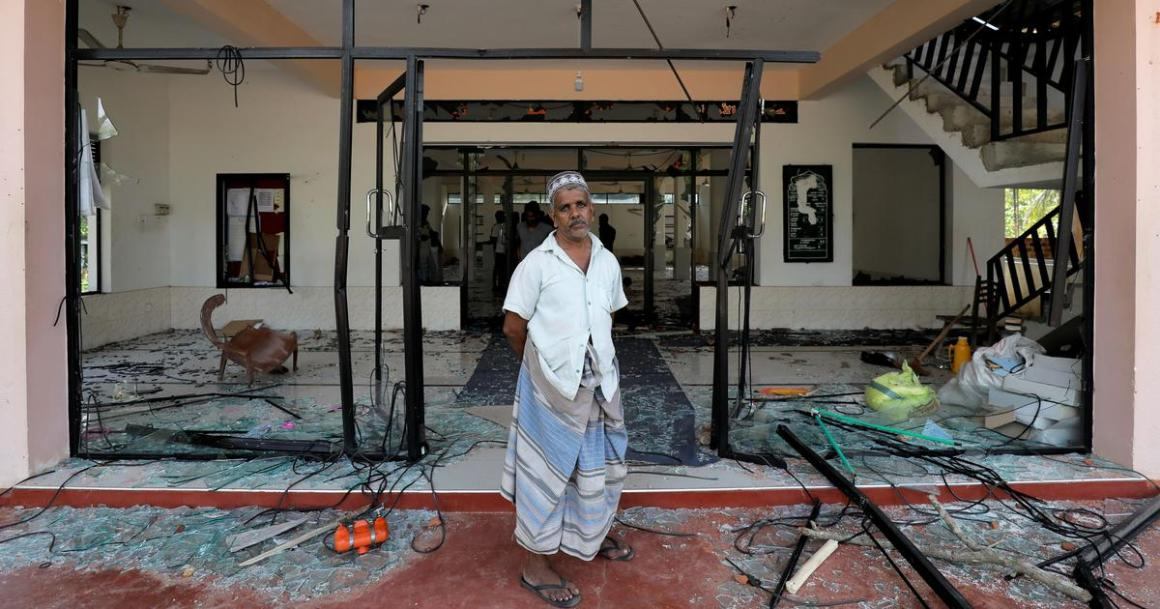 A Muslim man stands in front of the Abbraar Masjid mosque after a mob attack in Kiniyama, Sri Lanka, on May 13, 2019. | Dinuka Liyanawatte/Reuters