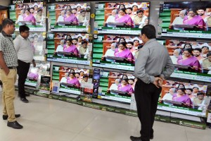 Kolkata: People watch Finance Minister Nirmala Sitharaman tabling the Union Budget 2019-20, on TV sets at a showroom in Kolkata, Friday, July 5, 2019. (PTI Photo) (PTI7_5_2019_000071B)