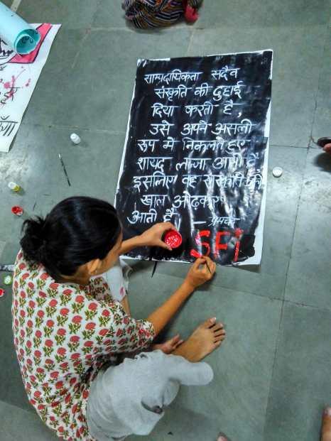 पोस्टर बनाती जेएनयू की एक छात्रा.