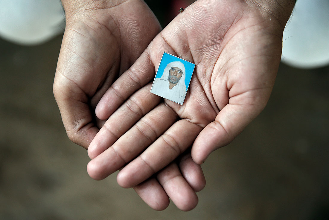 Irshad Khan, 24, holds a picture of his father Pehlu, who was beaten to death by a mob of Hindu vigilantes in April when transporting cattle back to his home in the village of Jaisinghpur. REUTERS/Cathal McNaughton