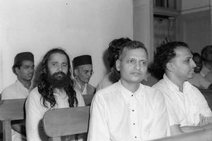 Photo taken during the trial of the persons accused of participation and complicity in Mahatma Gandhi's assassination in a Special Court in Red Fort, Delhi. The trial began on May 27, 1948. V.D. Savarkar, wearing a black cap, is seated in the last row, while Nathuram Godse and Narayan Apte are up front. Credit: Photo Division, GOI
