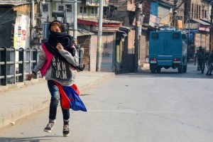 Srinagar:A girl runs for cover after throwing stones during a protest in Srinagar, Tuesday, Oct. 29, 2019. A delegation of 23 European Union MPs is on a visit to Jammu and Kashmir for a first-hand assessment of the situation in the Valley following the revocation of the state''s special status under Article 370. (PTI Photo) (PTI10_29_2019_000140A)
