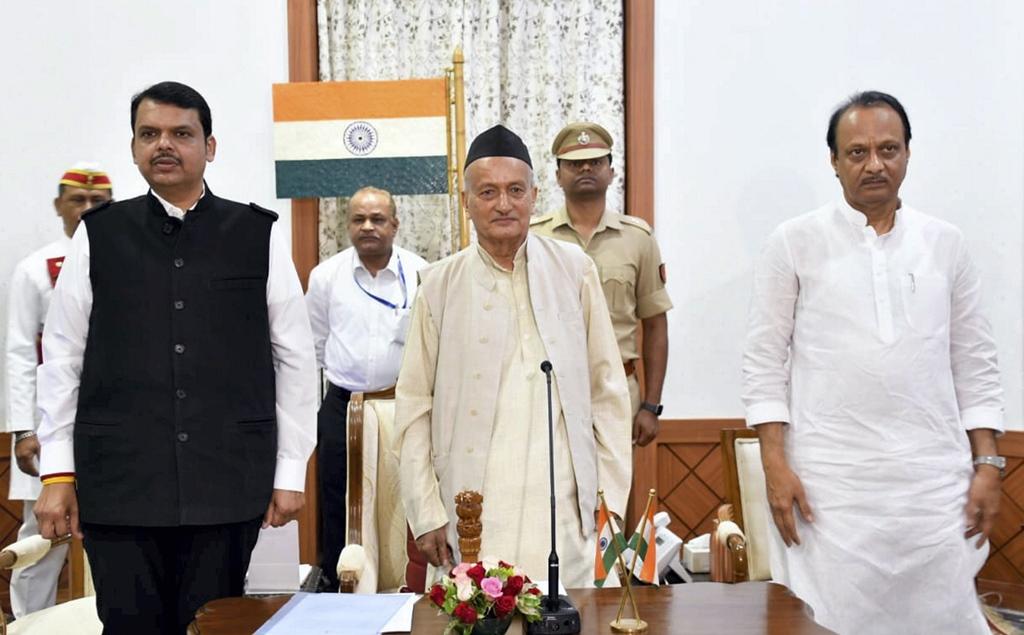 Mumbai: Maharashtra Governor Bhagat Singh Koshyari flanked by newly-appointed Chief Minister of Maharashtra Devendra Fadnavis and his Deputy CM Ajit Pawar, during an oath-taking ceremony, in Mumbai, Saturday, Nov. 23, 2019. (PTI Photo) (PTI11 23 2019 000027B)