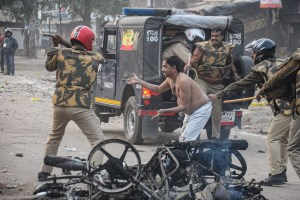 Kanpur: Police personnel hits a civilian during their protest against the Citizenship (Amendment) Act that turned violent, at Babu Purwa in Kanpur, Friday, Dec. 20, 2019. (PTI Photo) (PTI12_20_2019_000262B)