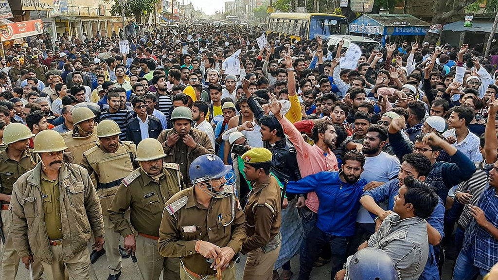 Mau: Police keep a watch as Muslim people shout slogans during a protest against Citizenship Amendment Act, at Mirza Hadipur Chowk in Mau, Monday, Dec. 16, 2019. (PTI Photo) (PTI12_16_2019_000237B)