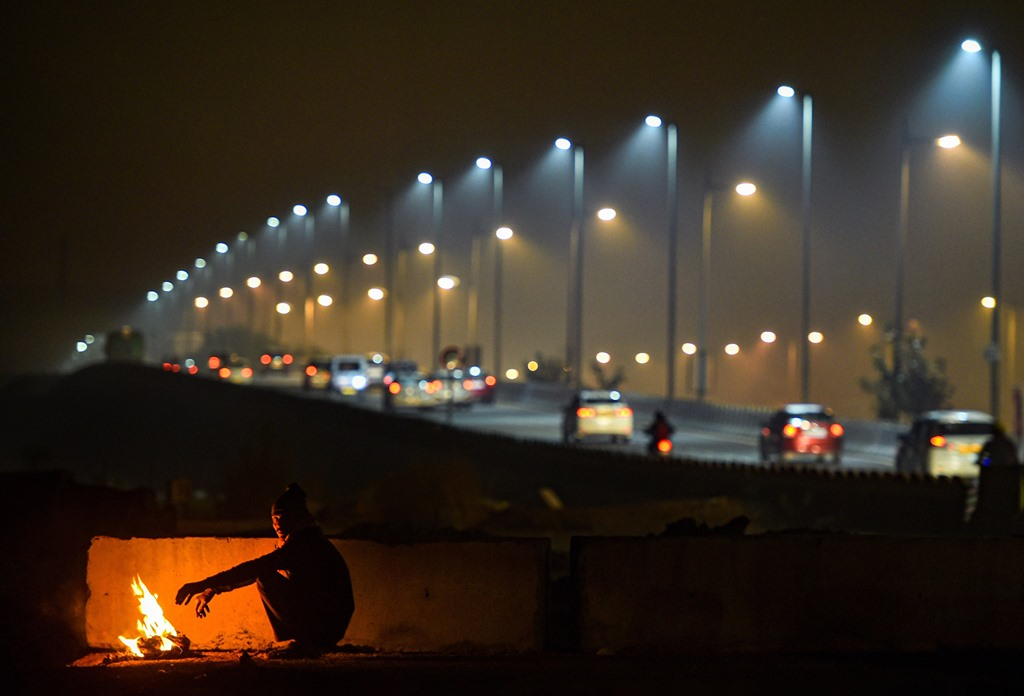 New Delhi: A man warms himself by a bonfire as cars ply in the background on a cold and wintry night, in New Delhi, Friday, Dec. 27, 2019. (PTI Photo/Arun Sharma)(PTI12_27_2019_000212B)
