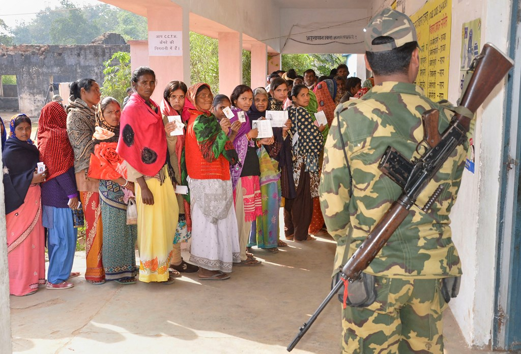 Bundu: A security jawan guards as people wait in queues to cast their votes at a polling station during the second phase of Jharkhand Assembly elections at Bundu, 45 kms from Ranchi, Saturday, Dec. 7, 2019. (PTI Photo) (PTI12_7_2019_000029B)