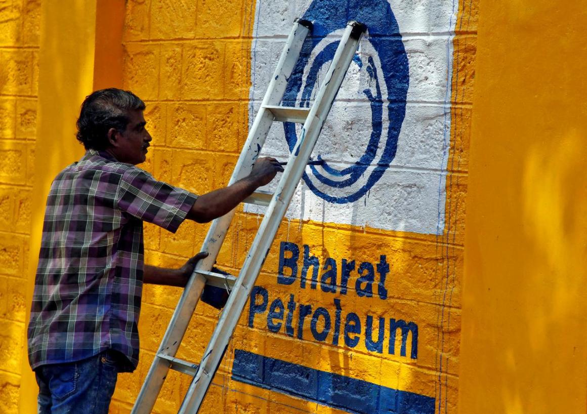 A man paints the logo of oil refiner Bharat Petroleum Corp (BPCL) on a wall on the outskirts of Kochi, India, November 21, 2019. REUTERS/Sivaram V/File Photo