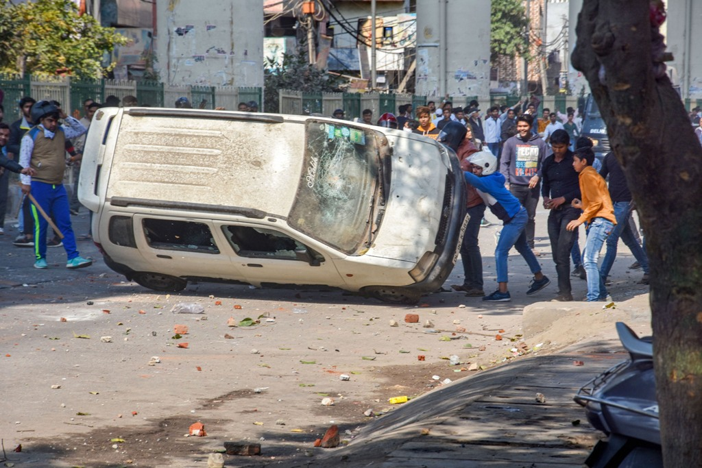New Delhi: Protestors vandalize a car during a clash between a group of anti-Citizenship Amendment Act protestors and supporters of the new citizenship act, at Maujpur crossing, in northeast Delhi, Monday, Feb. 24, 2020. (PTI Photi) (PTI2_24_2020_000165B)