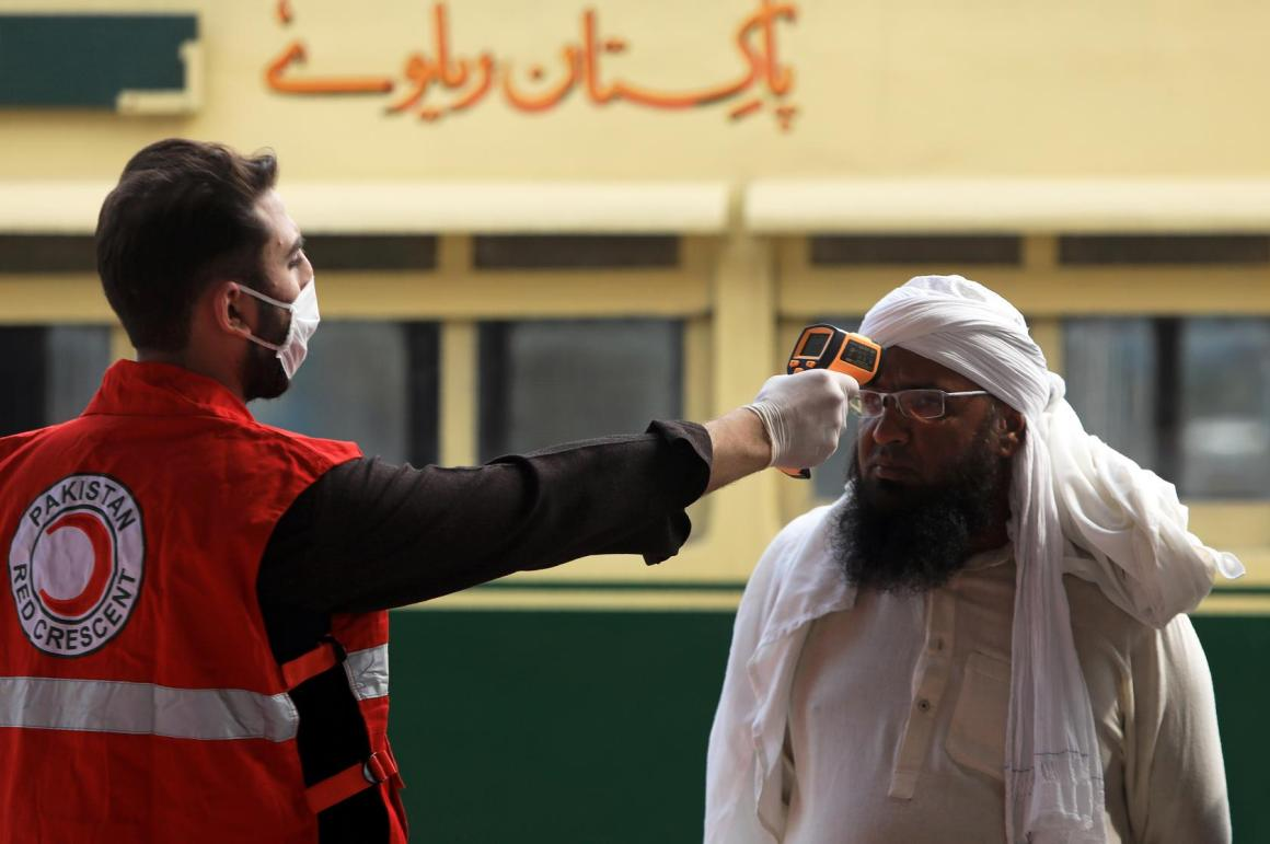 A worker checks a man's temperature following an outbreak of the coronavirus disease (COVID-19), at a railway station in Peshawar, Pakistan. (Reuters Photo)