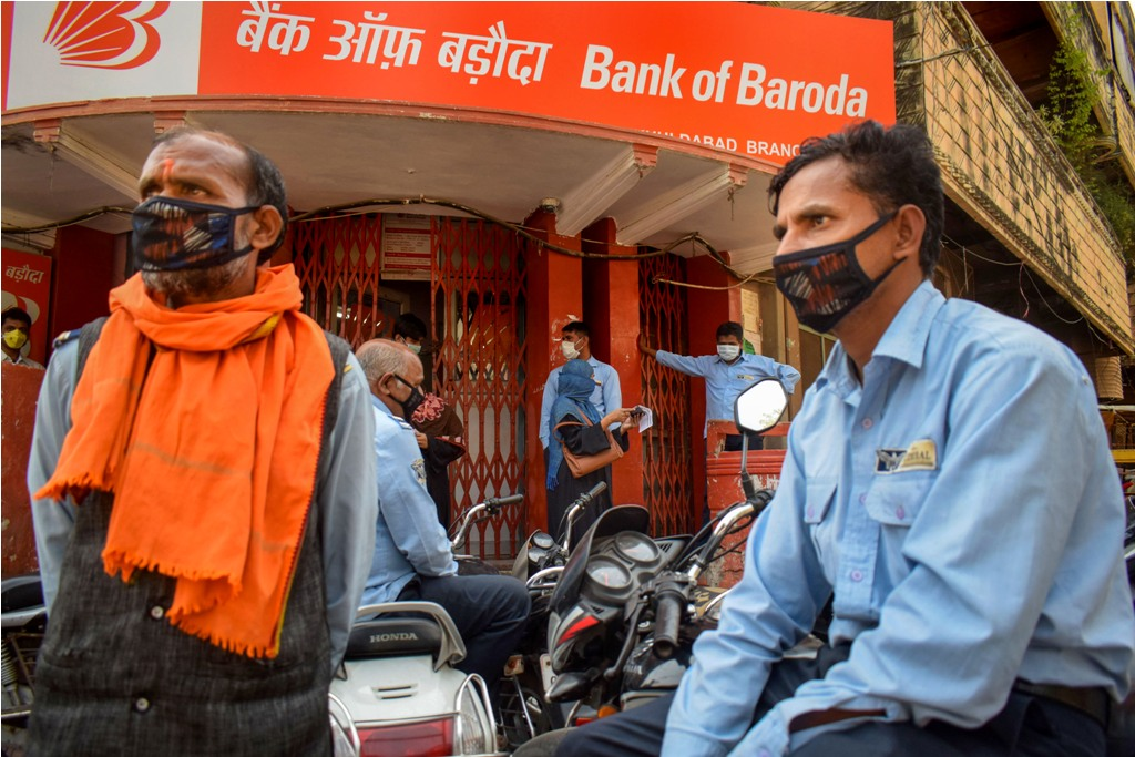 Prayagraj: People wearing protective masks mantain social distance as they wait outside a bank during a 21-day nationwide lockdown in the wake of coronavirus pandemic, in Prayagraj, Wednesday, March 25, 2020. (PTI Photo)(PTI25-03-2020 000194B)