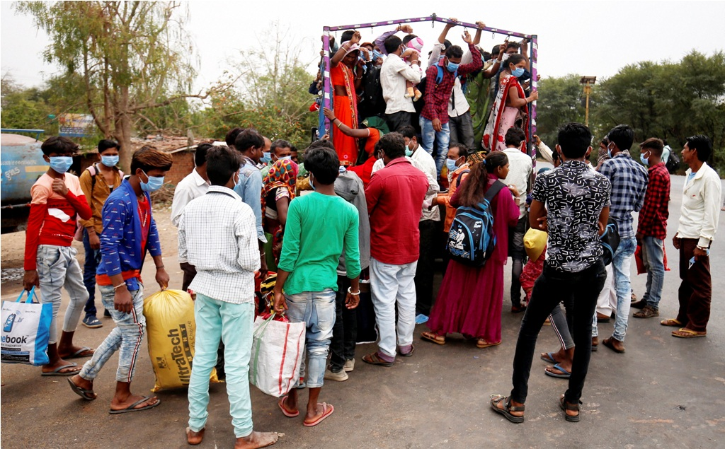 Ahmedabad: Migrant workers and their families board a truck to return to their villages after government imposed a 21-day nationwide lockdown in wake of coronavirus pandemic, in Ahmedabad, Wednesday, March 25, 2020. (PTI Photo)(PTI25-03-2020 000312B)