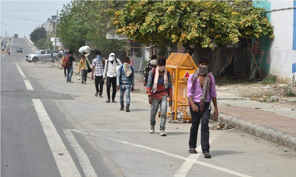 New Delhi: A group of migrant workers walk to their villages amid the nationwide complete lockdown, on the GT Road at Dilshan Garden in New Delhi, Thursday, March 26, 2020. The migrants, reportedly, started to foot it to their villages in Uttar Pradesh after they were left with no other option following the announcement of a 21-day lockdown across the country to contain the Covid-19, caused by the novel coronavirus. (PTI Photo/Manvender Vashist) (PTI26-03-2020 000032B)