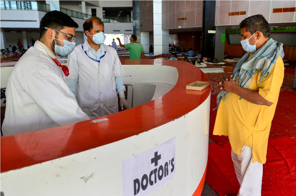 New Delhi: Doctors talk to a patient at a sports complex converted into a shelter during a nationwide lockdown in the wake of coronavirus pandemic, in New Delhi Friday, April 3, 2020. (PTI Photo/Kamal Kishore)(PTI03-04-2020 000098B)